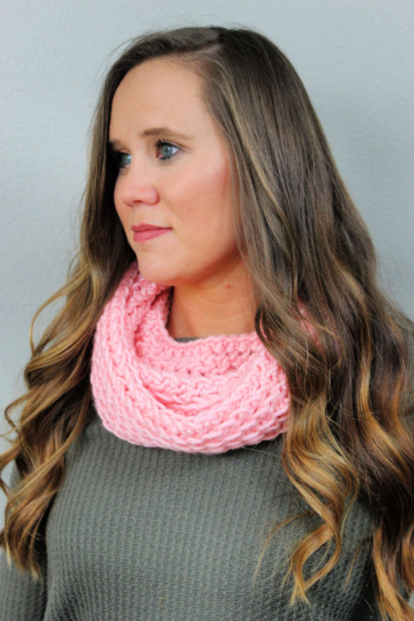 Woman wearing a pink crochet infinity scarf, called the KJ Infinity Scarf.