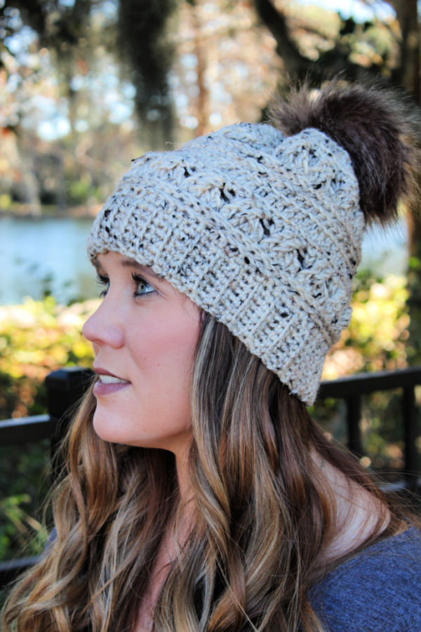 Woman wearing a crochet hat, called the Catherine Hat.