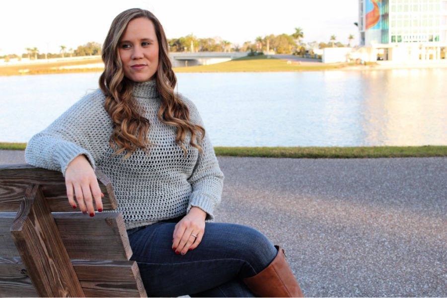 Woman sitting on a bench wearing a beginner crochet sweater, called the Bombshell Sweater.