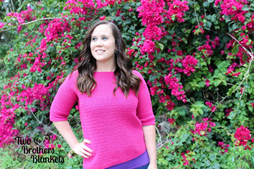 Woman wearing a pink crochet sweater, called the Springtime Sweater.