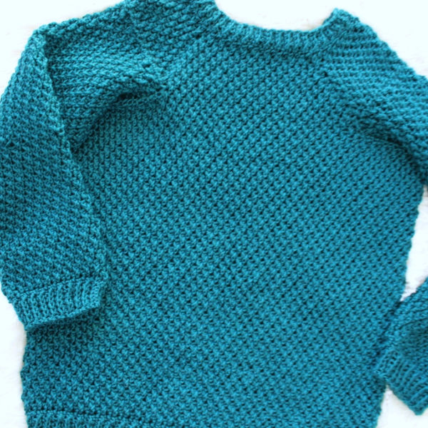 Flat lay of green crochet sweater, called the Savannah Sweater.