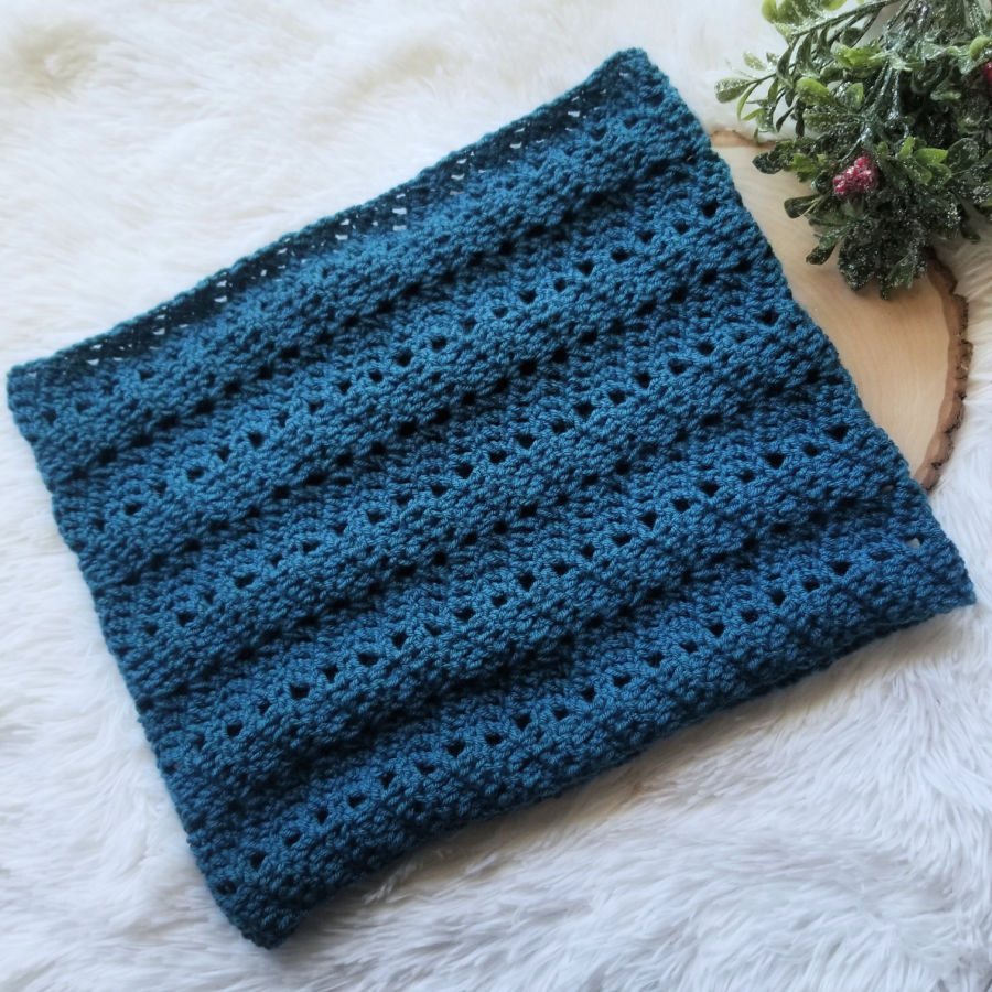 Flat lay of a green crochet cowl, called the Chevy Cowl. It is lying on a slab of wood with holly berries and leaves next to it.
