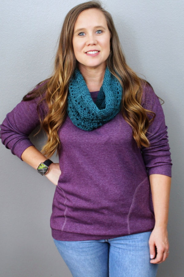 Woman wearing a green crochet cowl, called the Chevy Cowl.
