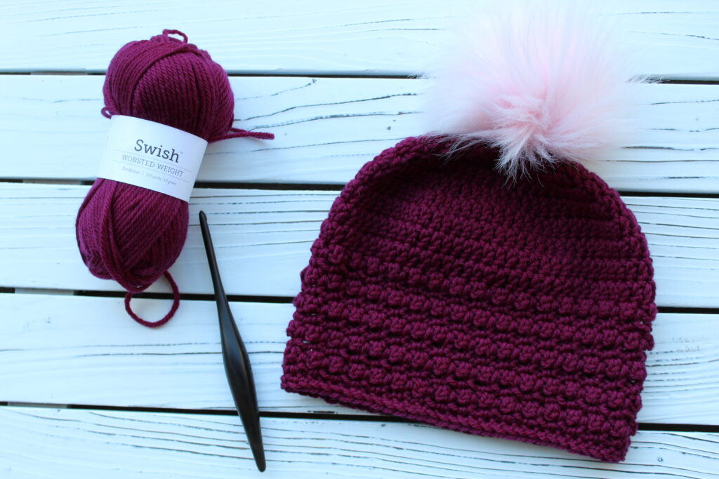 Flat lay of yarn, crochet hook, and crochet beanie in a dark pink color with a light pink pom.