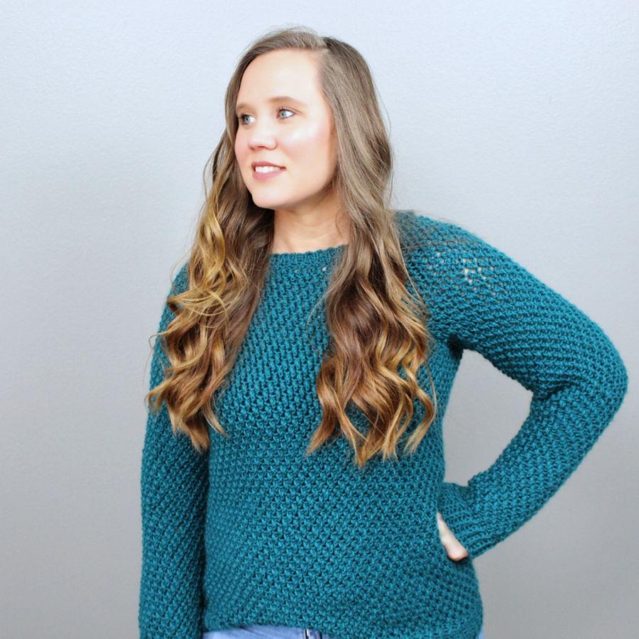 Woman wearing a green crochet sweater, called the Savannah Sweater.
