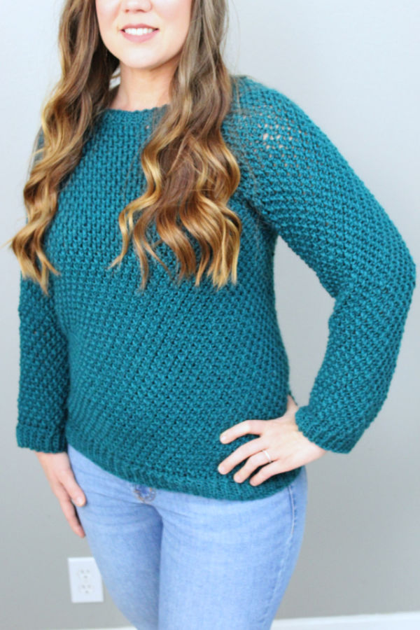 Close up of woman wearing a green crochet sweater, called the Savannah Sweater.