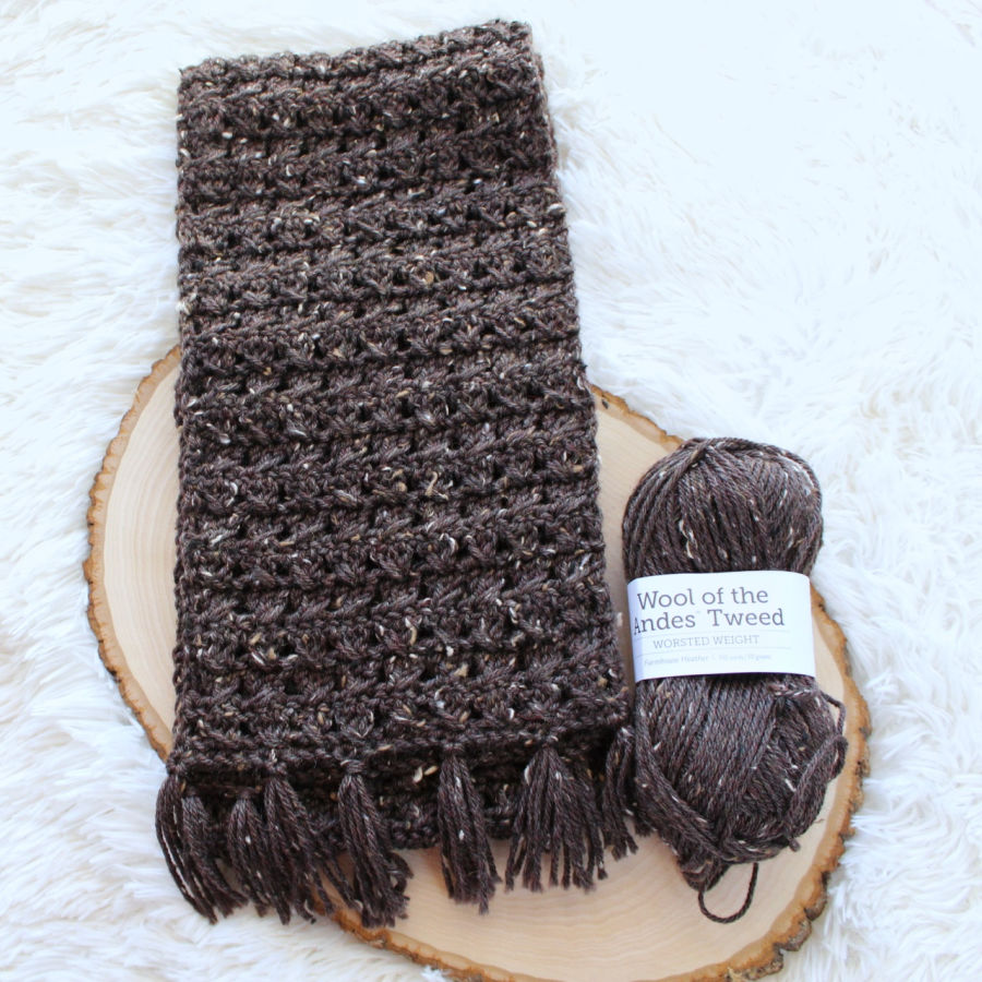 Flat lay of a brown crochet scarf with fringe and the yarn used to make it.