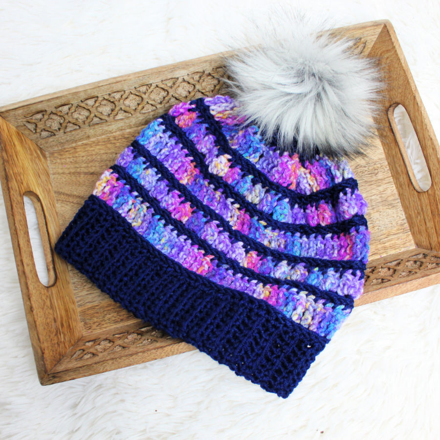 Multicolored crochet beanie with gray pom, called the Bobble Ridge Beanie.