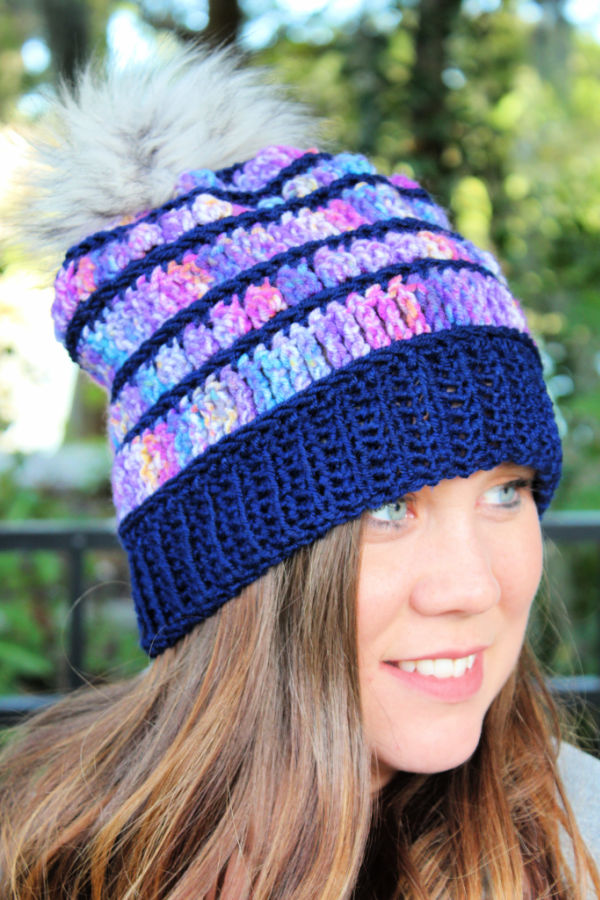 Woman wearing a crochet beanie that is purple and navy blue. This beanie is called the Bobble Ridge Beanie.