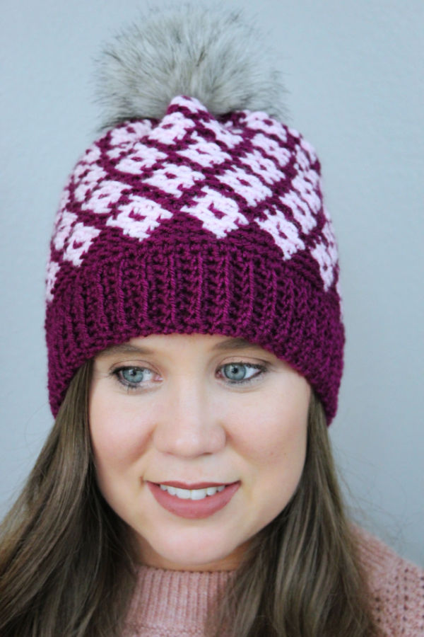 Close up of woman wearing a pink fair isle crochet hat, called the Illusion Hat.
