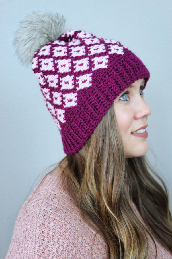 Women wearing a pink fair isle crochet hat, called the Illusion Hat.