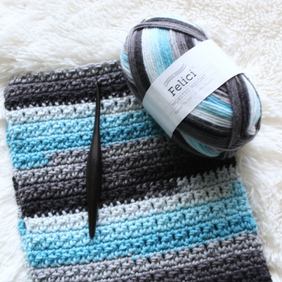 Close up of a crochet scarf, called the Friendship Scarf, with the yarn and crochet hook used to make it.