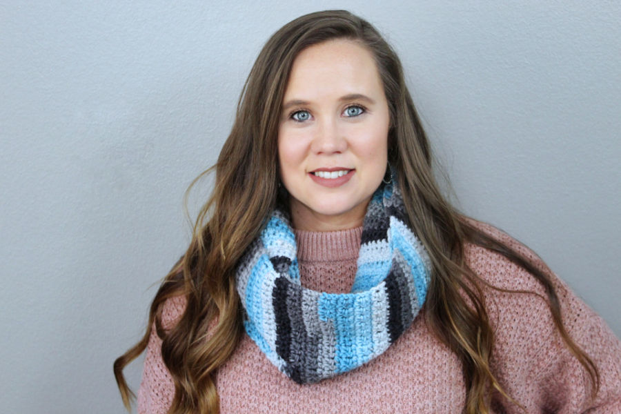 Woman wearing a crochet scarf called the Friendship Scarf.