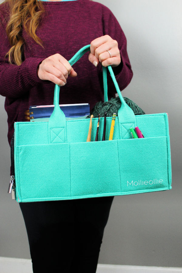 Woman holding a teal Mimmo Storage Caddy.