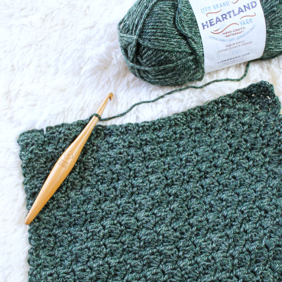 Flat lay photo of green Heartland yarn being made into a crochet scarf with a furls crochet hook.