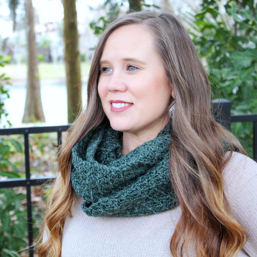 Woman wearing a green crochet scarf called the Ferguson Scarf.