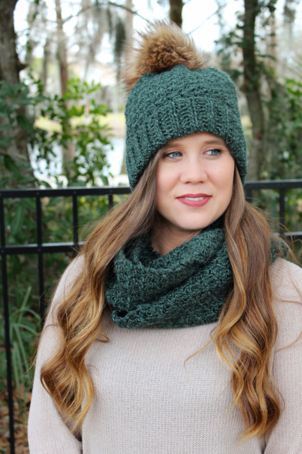 Woman wearing a green crochet hat and matching crochet scarf.