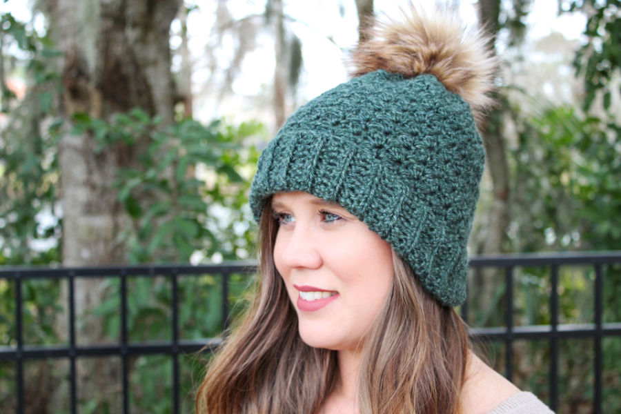 Woman wearing a green crochet hat with a brown pom. This hat is called the Ferguson Hat.
