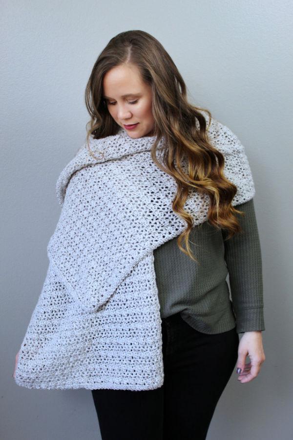 Woman wearing a long light gray crochet wrap, called the Katie Wrap.