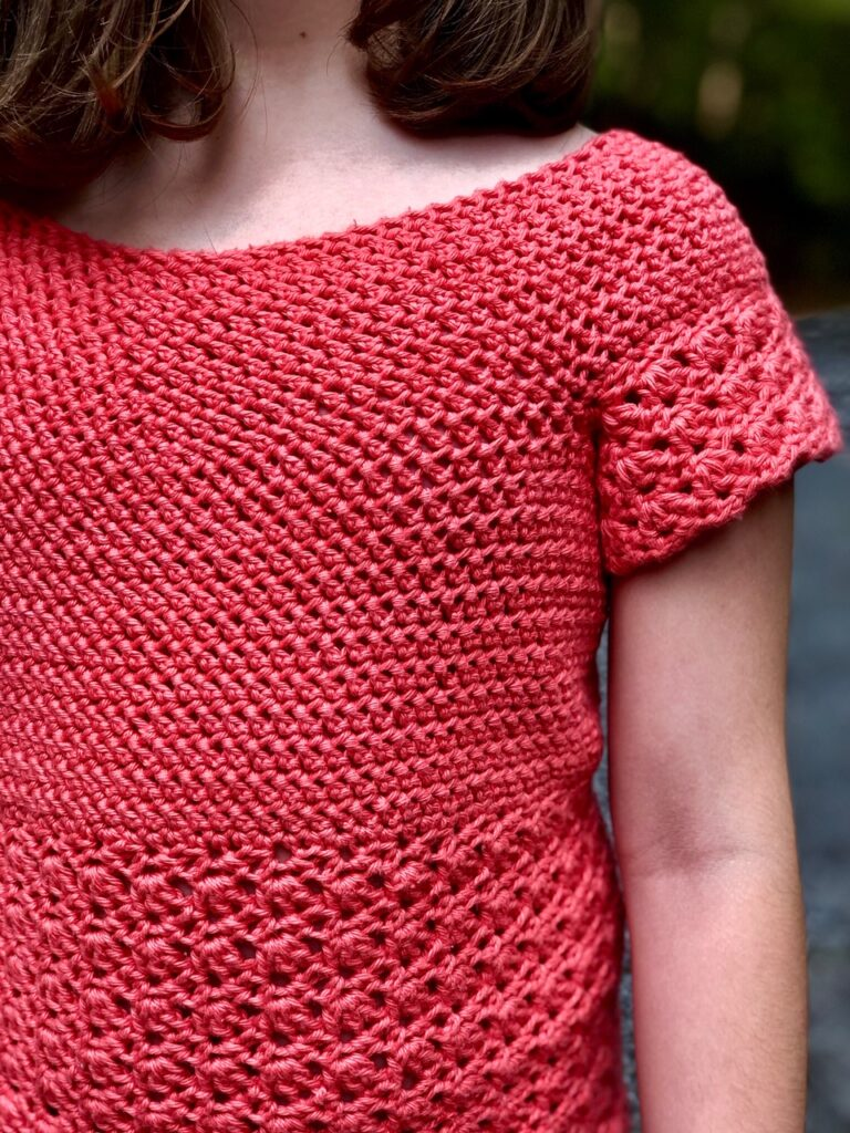 Close up of a children's crochet top, called the Primrose Blouse.