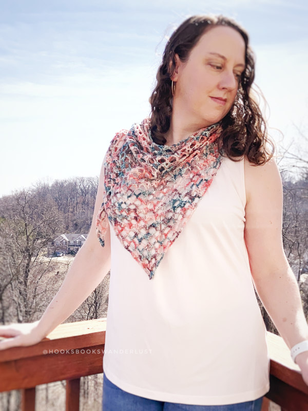 Woman wearing a crochet triangle shawl around her neck. This shawl is called the Iris Shawl.