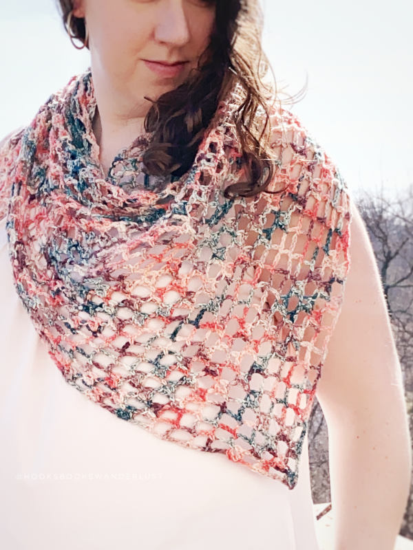 Woman wearing a crochet shawl called the Iris Shawl.