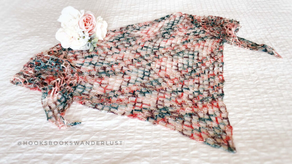 Flat lay photo of a crochet triangle shawl called the Iris Shawl.