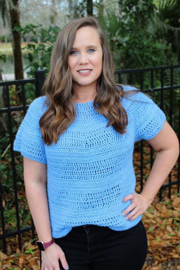 Woman wearing a light blue crochet top, called the Larkin Tee.