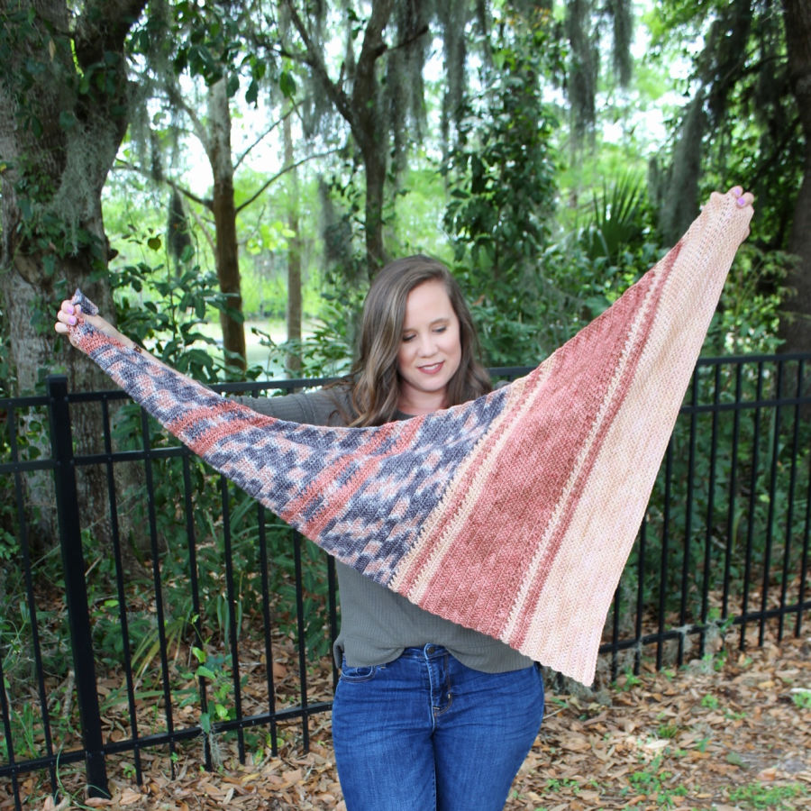 Woman holding up an asymmetrical crochet shawl, called the Amara Shawl.