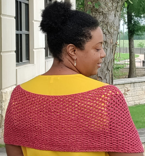 Woman wearing the Vintage Rose Crochet Scarf over her shoulders like a shawl.