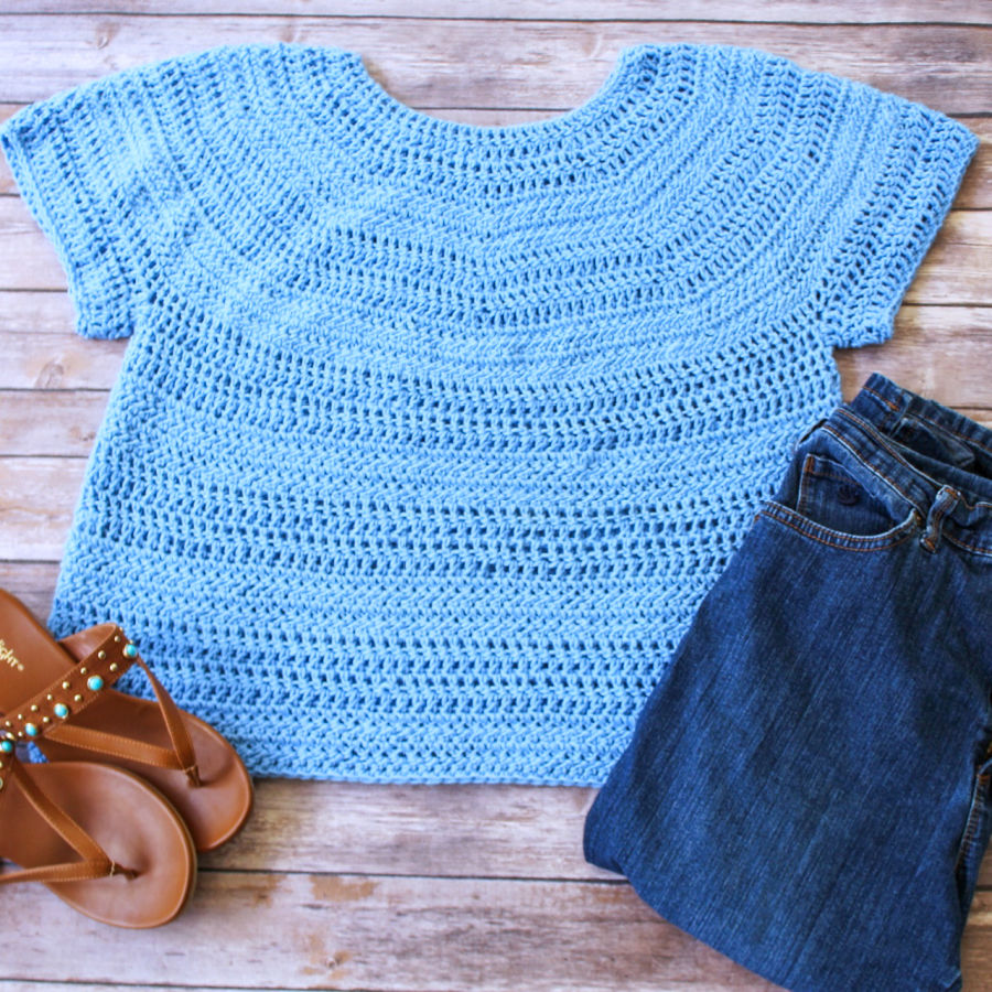Flatlay photo of a blue short sleeved crochet top, called the Larkin Tee. Top is photographed with jeans and sandals.