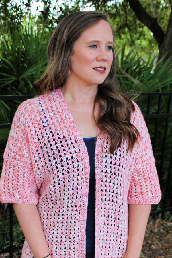 Close up view of a woman wearing a summer crochet cardigan, called the Jayda Cardigan.