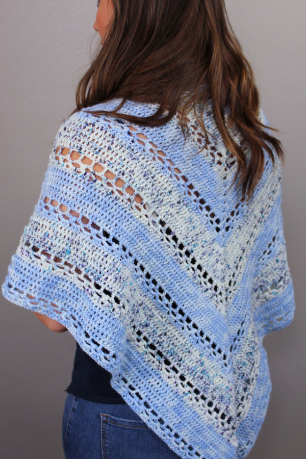 Woman wearing a blue crochet triangle shawl draped over her shoulders.