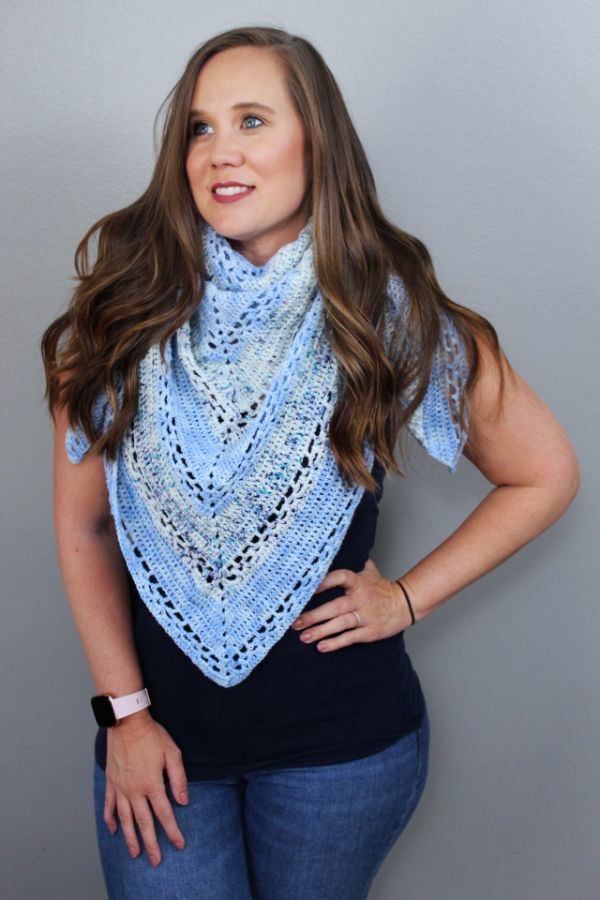 Woman wearing a blue crochet triangle shawl wrapped around her neck.