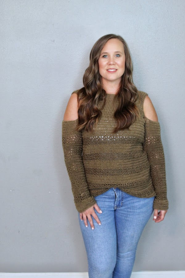 Woman wearing a crochet sweater called the Calgary Cold Shoulder pattern.