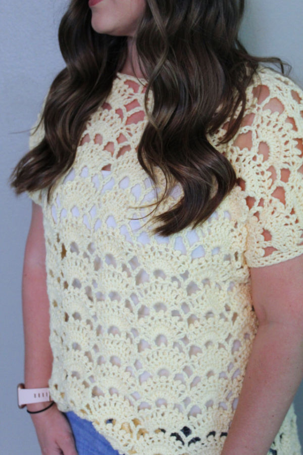 Close up photo of woman wearing a yellow crochet top, called the Santa Anna Tee.