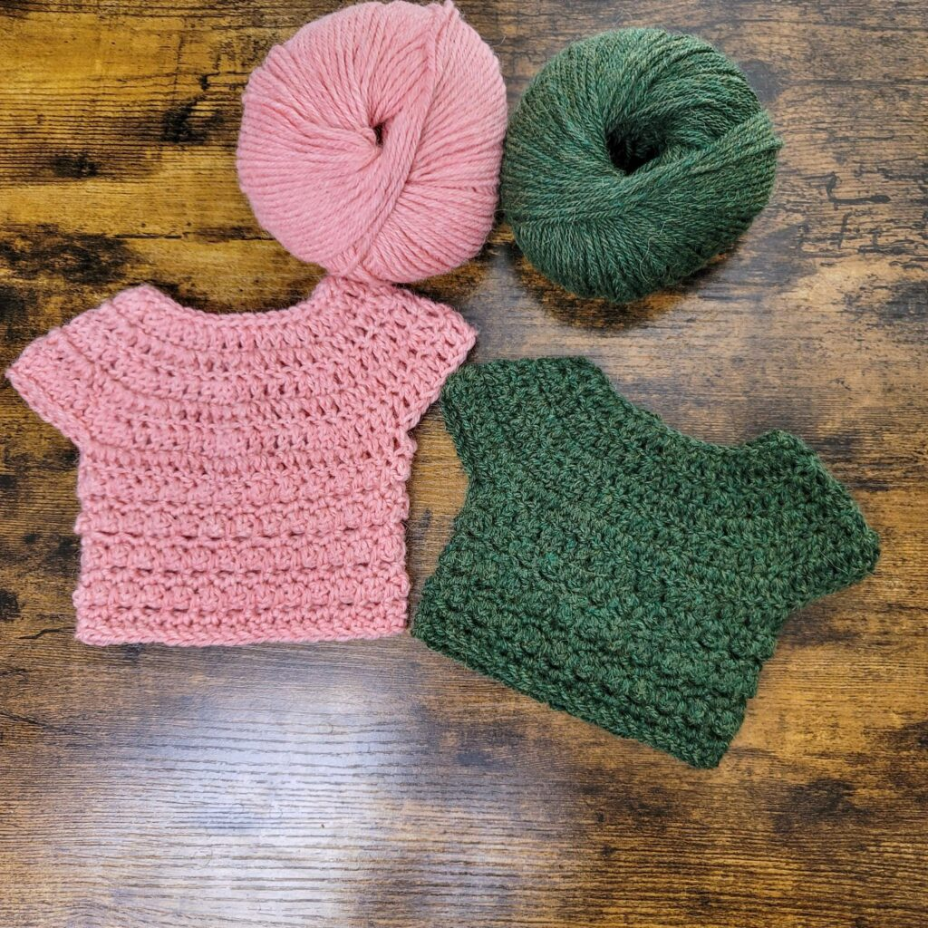 Two crochet baby sweaters lying next to the yarn used to make them.