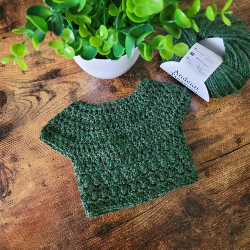 A green crochet baby sweater, called the Little Textures Baby Sweater.