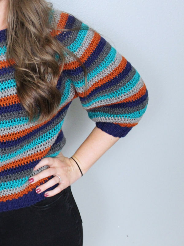 Close up of the sleeve of the Vinnie Sweater, a vintage striped crochet pattern.